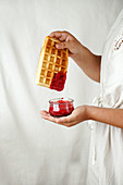 Woman holding waffle with red berry sauce