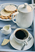 A cup of filter coffee with biscuits and pastries