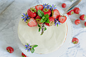 Yoghurt cake with tonka bean, strawberries and flower decoration