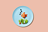 Underwater scene of a fish swimming created out of fruit
