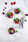 Small glasses with mascarpone cream and egg-free cream with cherries and blackberries