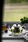 Mint tea in a glass teapot on a windowsill