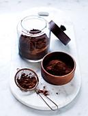 Kakaopulver in Sieb und verschiedenen Gefäßen