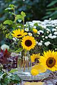 Spätsommerstrauß aus Sonnenblumen, Ligusterbeeren, Aster, Zweigen und Gräsern
