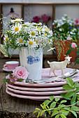 Strauß aus Margeriten, Schafgarbe und Gräsern in Milchbecher, Rosenblüte, Dolde vom Spierstrauch und Ziege als Tellerdeko
