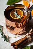 Apple cider heated in an antique copper pot, with oranges with leaves, orange slices, cinnamon sticks and sugared rosemary