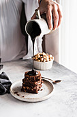 Pouring chocolate sauce on brownies
