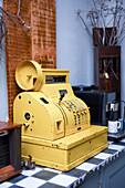 Alte Kasse aus Metall in Gelb als Vintage-Deko