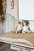 Teddy und Puppe auf einem alten Metallbett mit Jutematratze