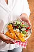 Polenta sticks with salad and Parmesan cheese