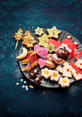 Assorted colourful Christmas biscuits on plates