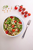 Farfalle salad with spinach, tomatoes and pine nuts