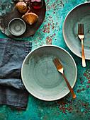 Grüne Keramikteller und goldene Gabeln (weihnachtlich)