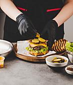 Essiggurken auf Cheeseburger anrichten