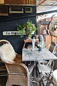 Korbstuhl mit Fell am Holztisch auf der Terrasse mit Vintage-Deko