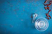 Glasmörser, Stössel und getrocknete Chilis auf blauer Holzoberfläche