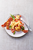 Scrambled eggs with tomatoes and crispy bacon