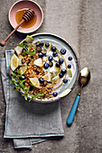 Breakfast bowl with blueberry yoghurt, granola, apple and mint