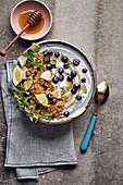 Frühstücksbowl mit Blaubeerjoghurt, Granola, Apfel und Minze