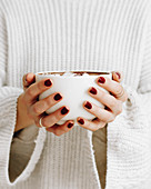 Woman holds a mug of hot chocolate with marshmallows