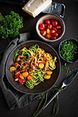 Yellow and green spaghetti with a colorful tomato and bacon sauce