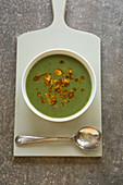 Green vegetable soup with chillied almond garnish