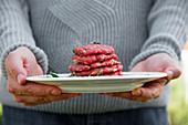 Mann hält Teller mit rohen Burger-Patties zum Grillen