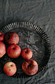 Fresh organic red apples in a vintage tart pan
