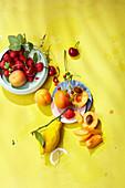 Zitronen, Aprikosen und frische Beeren auf gelbem Untergrund
