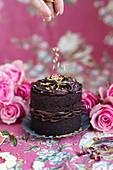 Mini chocolate cake is sprinkled with colorful sugar sprinkles