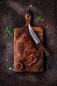 Grilled steak on a ceramic and wood board on marble table