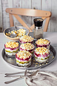 Herring salad with egg, beetroot, potatoes and pickled cucumbers