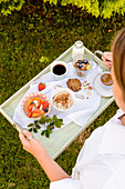 Woman carries a tray with healthy breakfast variations