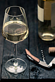 A glass of white wine with a bottle opener and wine bottle