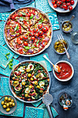 Two vegetarian pizzas with mushrooms, pepper, jalapeno, tomatoes, spinach, courgette, dried tomatoes