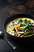 Thai hot and sour chicken soup with coconut milk, lime leaves, lemon grass, chilli and coriander