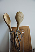 Wooden salad servers and herb scissors in a measuring cup