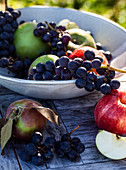 Bunches of concord grapes, and various varieties of green and red apples, in a bowl on a wooden table