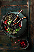 Black spaghetti with pak choy, pomegranate seeds and seaweed