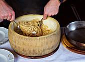 Stirring big cheek pasta in pecorino wheel