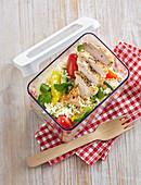 Couscous mit Hühnerbrust und Gemüse in Lunchbox zum Mitnehmen