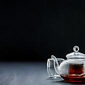 Schwarzer Tee in Glasteekanne vor schwarzem Hintergrund