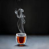 Dampfender schwarzer Tee in Glasbecher