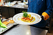 Chef holding plate of toast with poached egg, salmon and mustard sauce