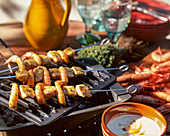 Chicken and prawn kebabs on a grill