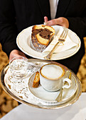 A waitress serves coffee and a piece of bundt cake