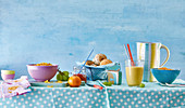 Breakfast table with rolls, juice, muesli and fruit for children