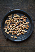 Toasted almonds in a round metal tray