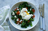 Kale salad with tomato, feta and poached eggs