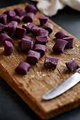 Rohe lila Süßkartoffelgnocchi auf Schneidebrett